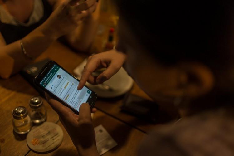 Garota em bar na Vila Madalena tenta, em vão, usar o WhatsApp (Foto: Avener Prado/Folhapress)