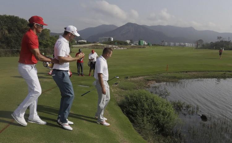 Golfistas observam uma capivara curtindo um banho em um lago do campo olímpico.